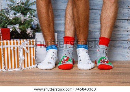 Closeup image of male feet in woolen socks on a wooden background. Hairy men's legs in New Year's socks.