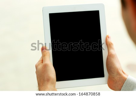 Closeup image of male hands showing display of tablet computer isolated on a white background - stock photo