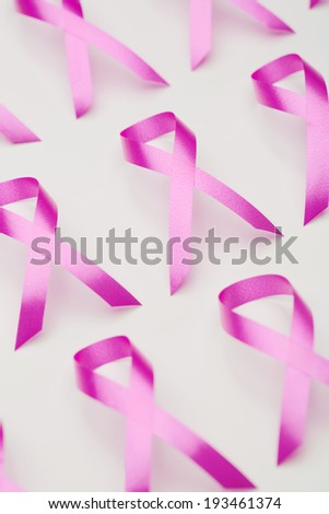 Closeup image of many pink ribbons next to each other over white, symbols of breast cancer awareness.