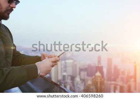 Closeup image of serious male entrepreneur is typing text message in network via mobile phone for his manager during business trip in New York,while is standing on cityscape background with copy space - stock photo