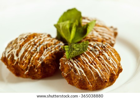 Closeup image of tasty brown muffins decorated with fresh mint leafs isolated at white background. - stock photo
