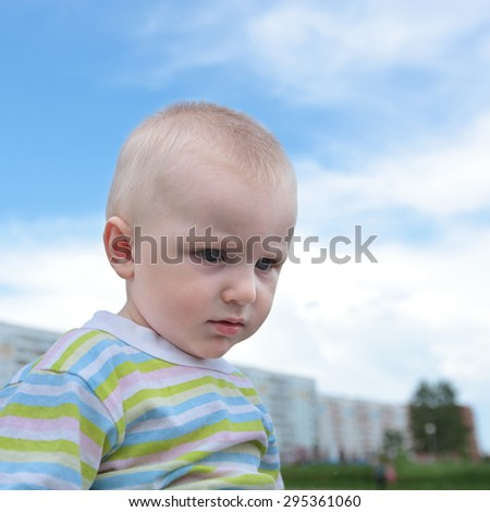 closeup image of the cute little baby over the blue sky background - stock photo