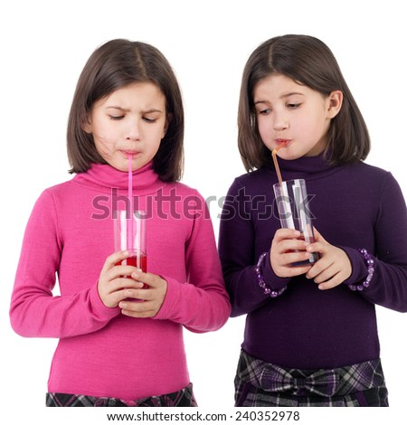 closeup image of the cute little twin sisters drinking juice - stock photo