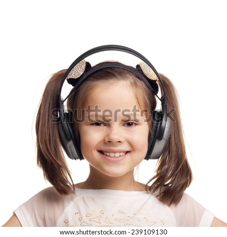 closeup image of the pretty smiling cute little girl wearing the headphones - stock photo