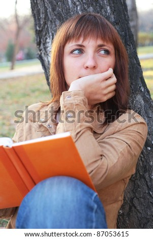 closeup image of the pretty young girl reading a book and dreaming in the park - stock photo