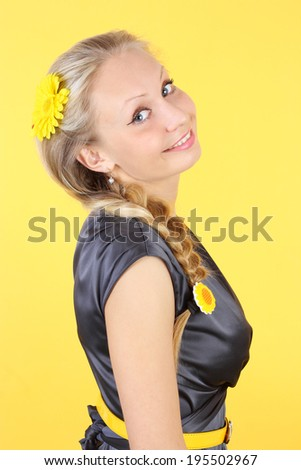 closeup image of the young beautiful blond girl on the yellow background