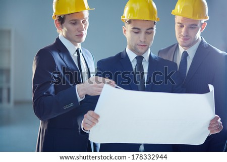 Closeup image of three constructors developing the business project  - stock photo