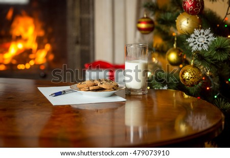 Closeup image of treats and letter to Santa on wooden table next Christmas tree and burning fireplace