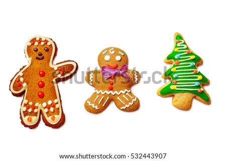 Closeup image of two gingerbread men and christmas tree isolated at white background.