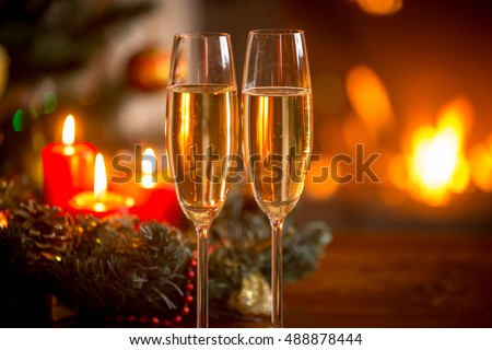 Closeup image of two glasses of champagne in front of Christmas wreath and burning fireplace