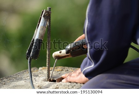 Closeup image of welder working on roof of the house  - stock photo