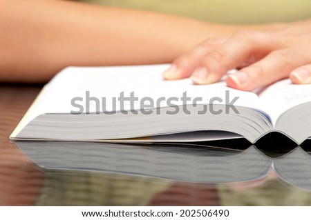Closeup image of woman hands holding open book - stock photo