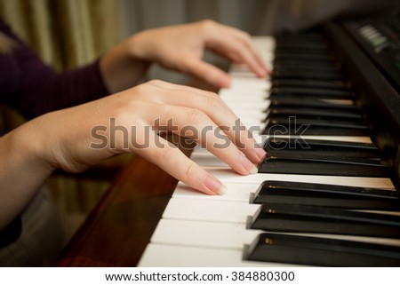 Closeup image of young woman playing on piano - stock photo