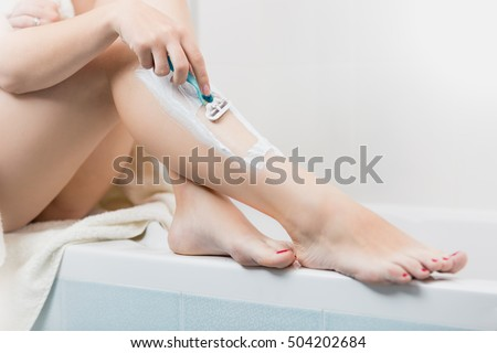 Closeup image of young woman removing hair on legs with razor at bathroom