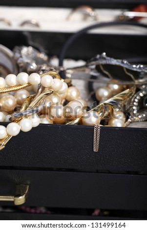 Closeup image with shallow dof of two pearl necklaces and assorted other jewellery and gold chains overflowing from a jewellery box - stock photo