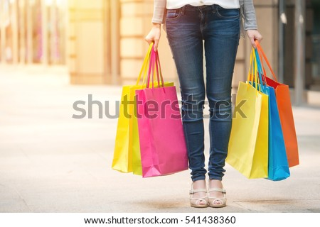 closeup images concept of woman standing shopping and holding vibrant color paper bags, Mixed race Asian female model
