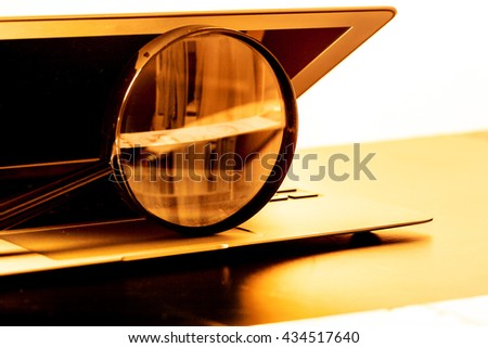 Closeup images of magnifying glass on laptop keyboard - stock photo