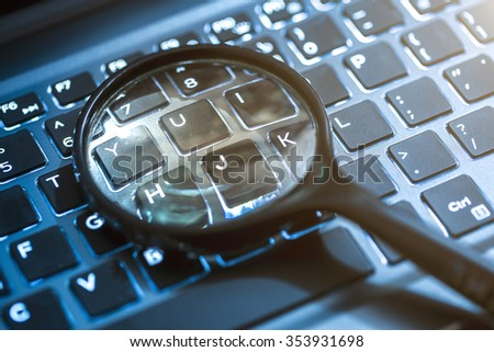 Closeup images of magnifying glass on laptop keyboard, searching, online shopping, and business concept