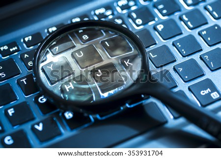 Closeup images of magnifying glass on laptop keyboard, searching, online shopping, and business concept - stock photo