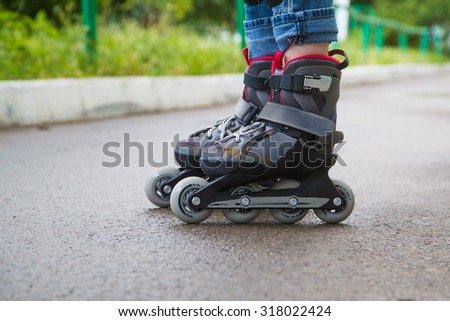 Closeup  inline skates  on the legs over the wet asfalt. - stock photo