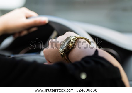 Closeup inside vehicle of woman's hand holding onto steering wheel, other arm showing off wrist watch, female driver concept