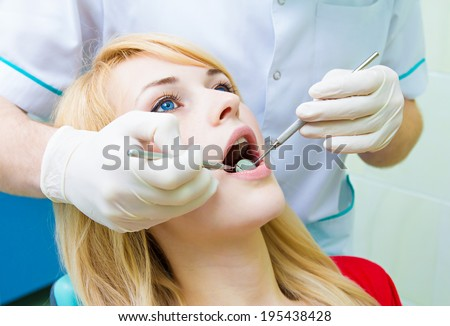 Closeup isolated portrait young female, beautiful blonde woman, patient sitting in dentist chair, office with wide open mouth getting oral thorough examination done by doctor in gloves, using mirror - stock photo