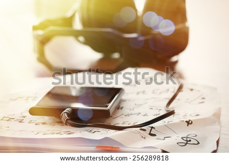 Closeup jack of smart phone with headphone on musical notes paper with shallow DOF evenly matched on wooden desk - stock photo