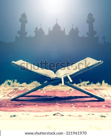 Closeup Koran, holy book of Muslim over blurred beautiful mosque. - stock photo