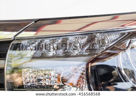 Closeup LED headlights daylight running of modern white car - stock photo