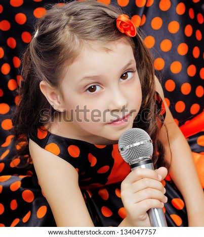 Closeup little girl in orange peas dress with microphone