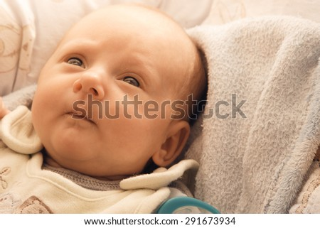 Closeup little newborn baby girl three weeks lying in diaper with open eyes