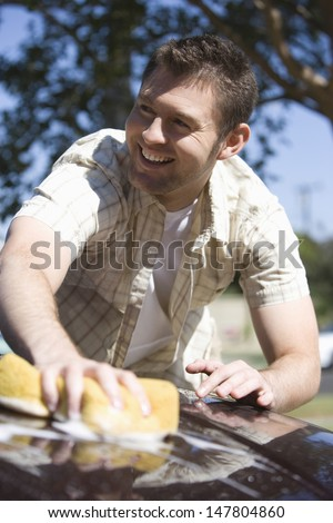 Closeup low angle view of a smiling man washing cropped car - stock photo