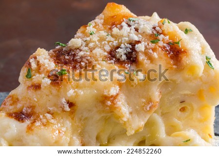 Closeup macro cheesy baked macaroni and cheese pasta portion with parmesan sprinkled on top - stock photo