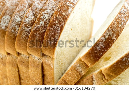 Closeup macro of loaf of bread with slices - stock photo