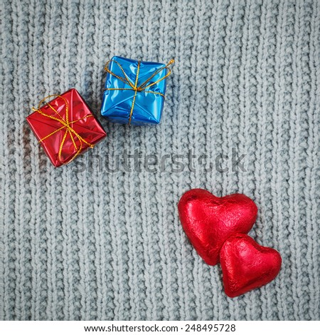 Closeup macro texture of grey knitted wool fabric material shawl scarf background with two red candies hearts on top and red and blue gift boxes presents, Valentine holiday card, love romance concept - stock photo