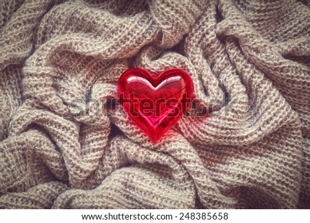 Closeup macro texture of knitted wool fabric material with lonely red shiny smooth heart on top, clothing background with wrinkles and folds, Valentine holiday card - stock photo