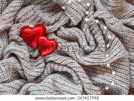 Closeup macro texture of knitted wool fabric material with red candy heart and white pearl  bead necklace on top, clothing background with wrinkles and folds, Valentine holiday card, love concept - stock photo