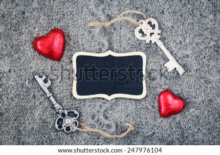 Closeup macro texture of knitted wool gray shawl with two red hearts, Victorian keys and wooden plate board plaque with copy space for text, Valentine holiday card, love concept - stock photo