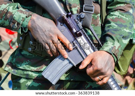 closeup male soldier hands holding machine gun, selective focus on hand. - stock photo