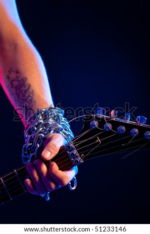 closeup man hand with tatoo and chain holding guitar