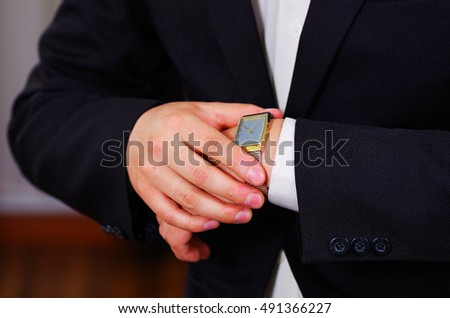 Closeup man's arm wearing suit, adjusting silver wrist watch using hands, men getting dressed concept