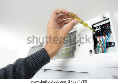 closeup man's hand checking air conditioner in the room - stock photo