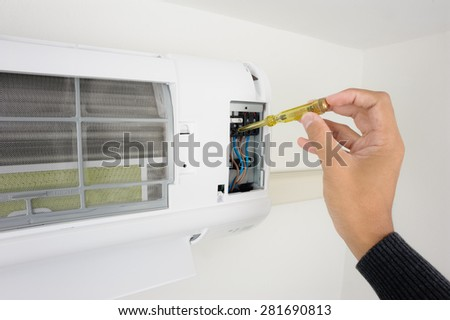 closeup man's hand checking air conditioner in the room