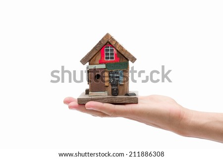Closeup. Man's hand holding house isolated on white background - stock photo