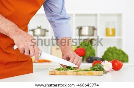 Closeup man's hand with a knife cutting  green onion on a wooden board. Healthy eating, vegetarian food, cooking, dieting and people concept.