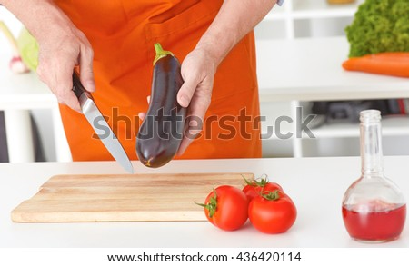 Closeup man's hands cutting vegetables on a work surface in a kitchen. Dieting Concept. Healthy Lifestyle. Cooking At Home. Prepare Food. - stock photo