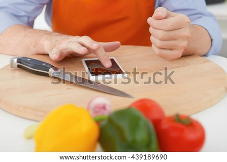 Closeup man's hands  pointing finger on phone before cutting vegetables on a work surface in a kitchen. Cooking, technology and home concept  - stock photo
