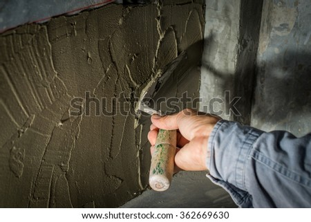 Closeup mason hand spreading fresh concrete mix with trowel - stock photo