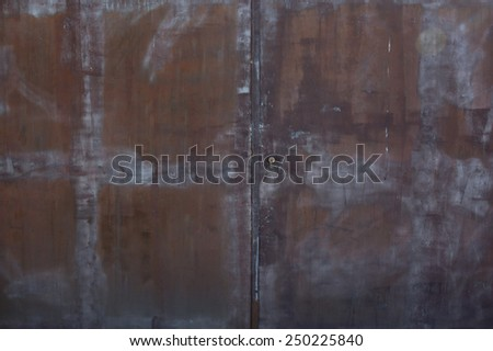 Closeup metal door with lock in grungy rusted style and good texture. - stock photo
