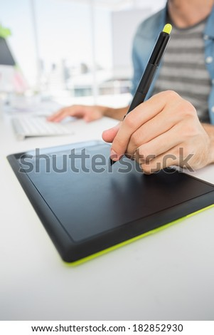 Closeup mid section of a casual male photo editor using graphics tablet in a bright office